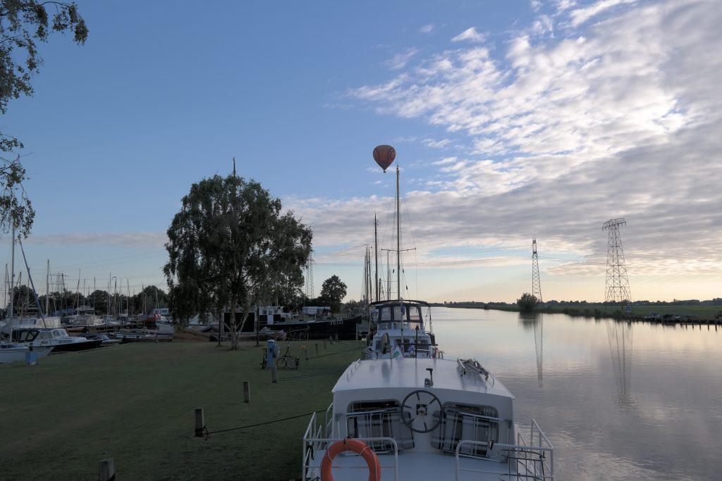 Sonnenuntergang mit Heißluftballon im Hafen in Akkrum mit Heißluftballon.