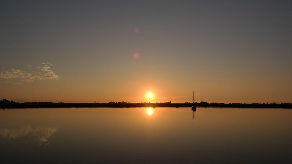 Sonnenuntergang am See mit Segelboot.